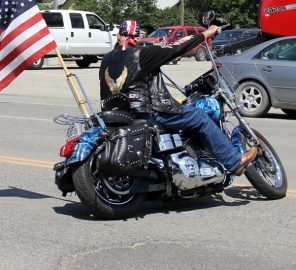 Motorcycle rider at the 4th July Parade with flag a Link to the Visitors page